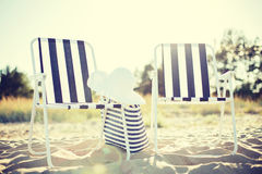 Two beach lounges with beach bag and white hat Royalty Free Stock Images