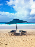 Two beach lounges with umbrella in tropical beach Royalty Free Stock Photo