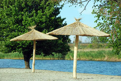 Two beach umbrellas on the river bank Royalty Free Stock Photo