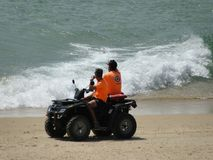 Two beach watchers in their vehicle. Two beach guards in their vehicle prepared to rescue bathers in the sea royalty free stock photo