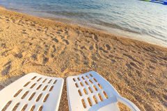 Two beachchairs on the sand near sea, closeup Royalty Free Stock Photography