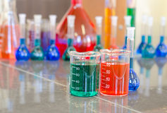 Two beakers filled with chemicals Stock Photos