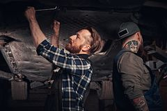 Two bearded auto mechanic in a uniform repair the car`s suspension while standing under lifting car in the repair garage. Two bearded auto mechanic in a uniform stock image