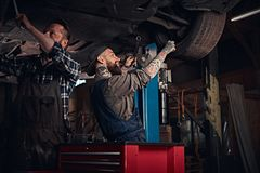 Two bearded auto mechanic in a uniform repair the car`s suspension while standing under lifting car in the repair garage. Two bearded auto mechanic in a uniform stock photo