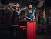 Two bearded auto mechanic in a uniform repair the car`s suspension while standing under lifting car in the repair garage. Two bearded auto mechanic in a uniform royalty free stock photo