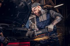 Two bearded auto mechanic in a uniform and safety glasses working with an angle grinder while standing against a broken. Car in the repair garage Stock Image