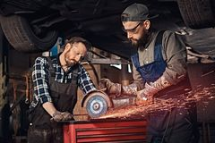 Two bearded auto mechanic in a uniform and safety glasses working with an angle grinder while standing under lifting car. In a repair garage Stock Photos
