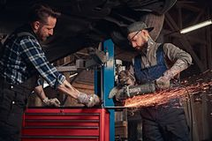 Two bearded auto mechanic in a uniform and safety glasses working with an angle grinder while standing under lifting car. Two bearded auto mechanics in a uniform Royalty Free Stock Photography