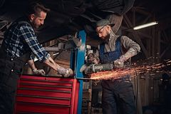Two bearded auto mechanic in a uniform and safety glasses working with an angle grinder while standing under lifting car. In a repair garage Royalty Free Stock Image