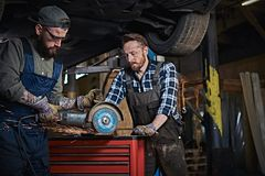 Two bearded auto mechanic in a uniform and safety glasses working with an angle grinder while standing under lifting car. Two bearded auto mechanics in a uniform Stock Photography