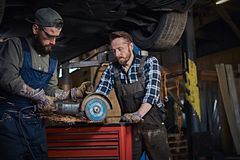 Two bearded auto mechanic in a uniform and safety glasses working with an angle grinder while standing under lifting car. In a repair garage Stock Photography