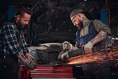 Two bearded auto mechanics in a uniform and safety glasses working with an angle grinder while standing against a broken. Car in the repair garage Stock Photos