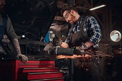 Two bearded auto mechanics in a uniform and safety glasses working with an angle grinder while standing against a broken. Car in the repair garage Royalty Free Stock Photos