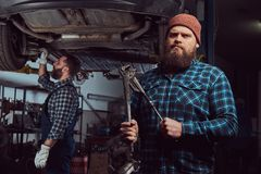 Two bearded brutal mechanics repair a car on a lift in a garage. royalty free stock images