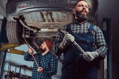 Two bearded brutal mechanics repair a car on a lift in a garage. royalty free stock photo