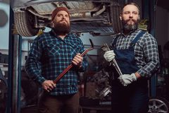 Two bearded brutal mechanics repair a car on a lift in a garage. stock photos
