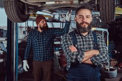 Two bearded brutal mechanics repair a car on a lift in the garage. stock photo
