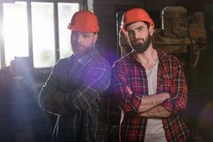 two bearded carpenters with crossed hands in protective helmets standing stock image