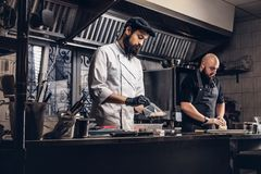 Two brutal cooks dressed in uniforms preparing sushi in a kitchen.