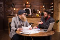 Two bearded economists having a business meeting in a coffee shop. Caucasian men. Handsome men. Good team work royalty free stock photography