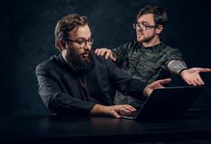 Two bearded hacker arguing showing hands to laptop. In the studio on a black background stock photos