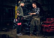 Two bearded  mechanics inspecting car`s engine parts. Two bearded tattooed mechanics inspecting car`s engine parts in a garage Stock Images