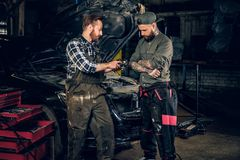 Two bearded  mechanics inspecting car`s engine parts. Two bearded tattooed mechanics inspecting car`s engine parts in a garage Royalty Free Stock Image