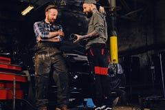 Two bearded  mechanics inspecting car`s engine parts. Two bearded tattooed mechanics inspecting car`s engine parts in a garage Stock Image