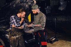 Two bearded  mechanics inspecting car`s engine parts. Two bearded tattooed mechanics inspecting car`s engine parts in a garage Stock Photo