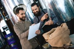 Two bearded men check quality of the malt. Workers of brewery conduct product analysis. stock photo