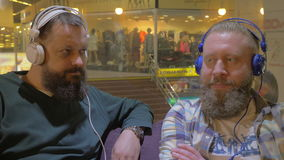 Two bearded men listening to music in headphones. Two mature bearded men in headphones relaxing with music in shopping mall stock video