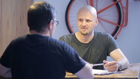 Two bearded men sit at wooden table and speak with each other. One of them has bald head and wears little earring in his left ear. It demonstrates him as stock footage