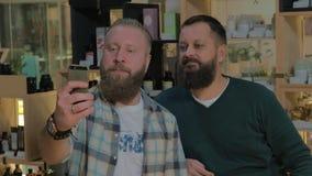 Two bearded men taking mobile selfie indoor. Two mature bearded men taking cellphone selfie in the barbershop stock video