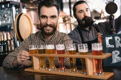 Two bearded men test beer of different styles in beer samplers in brewery of craft beer. royalty free stock images