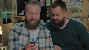 Two bearded men using smart phone. Two mature bearded men browsing web on cell and talking while waiting in the barbershop stock footage