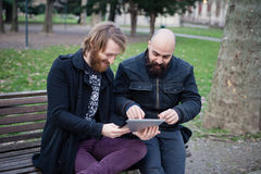 Two bearded modern man working on tablet Royalty Free Stock Images