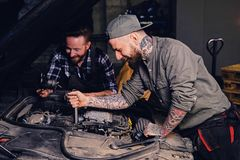 Two mechanics fixing car`s engine in a garage. Two bearded tattooed mechanics fixing car`s engine in a garage Royalty Free Stock Images