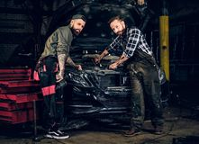 Two mechanics fixing car`s engine in a garage. Two bearded tattooed mechanics fixing car`s engine in a garage Stock Photo