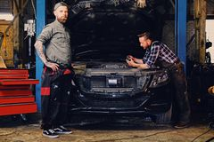 Two mechanics fixing car`s engine in a garage. Two bearded tattooed mechanics fixing car`s engine in a garage Royalty Free Stock Photo