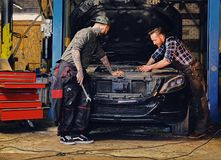 Two mechanics fixing car`s engine in a garage. Two bearded tattooed mechanics fixing car`s engine in a garage Stock Images