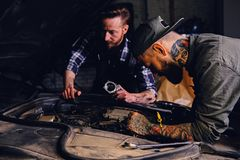 Two mechanics fixing car`s engine in a garage. Two bearded tattooed mechanics fixing car`s engine in a garage Royalty Free Stock Photos