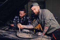 Two mechanics fixing car`s engine in a garage. Two bearded tattooed mechanics fixing car`s engine in a garage Stock Image