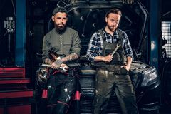 Two bearded tattooed mechanics near the car in a workshop. Two bearded tattooed mechanics with nut key near the car with open engine hood in a workshop Stock Image
