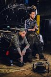 Two bearded tattooed mechanics near the car in a workshop. Two bearded tattooed mechanics with nut key near the car with open engine hood in a workshop Royalty Free Stock Images