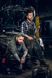 Two bearded tattooed mechanics near the car in a workshop. Two bearded tattooed mechanics with nut key near the car with open engine hood in a workshop Stock Photo