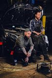 Two bearded tattooed mechanics near the car in a workshop. Two bearded tattooed mechanics with nut key near the car with open engine hood in a workshop Stock Photography