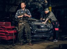 Two bearded tattooed mechanics near the car in a workshop. Two bearded tattooed mechanics with nut key near the car with open engine hood in a workshop Royalty Free Stock Image