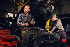 Two bearded tattooed mechanics near the car in a workshop. Two bearded tattooed mechanics with nut key near the car with open engine hood in a workshop Royalty Free Stock Photos