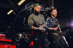 Two bearded tattooed mechanics near the car in a workshop. Two bearded tattooed mechanics with nut key near the car with open engine hood in a workshop Stock Photos