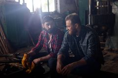 two bearded workers sitting and talking to each other stock images